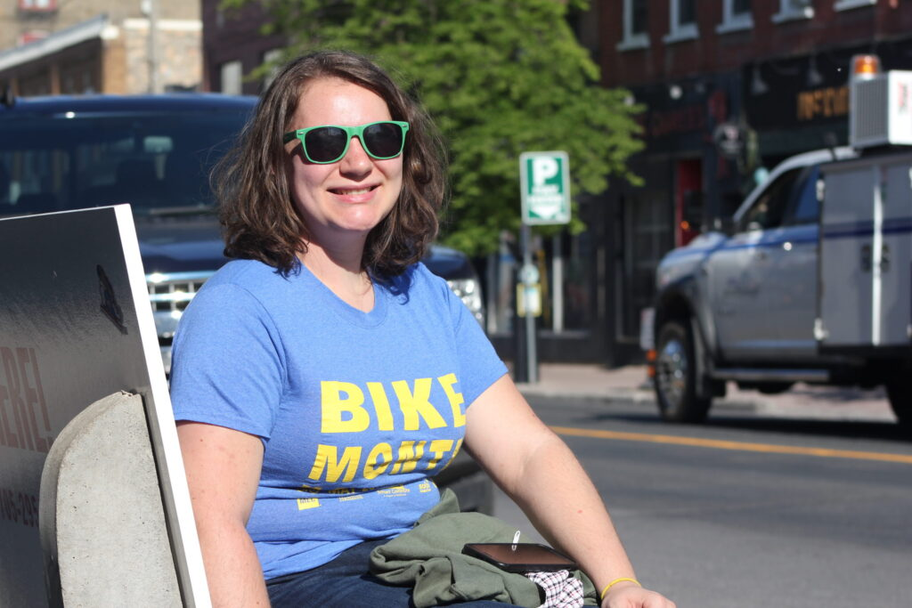 A woman in sunglasses sits on a bench by a city street.